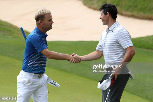 Soren Kjeldsen of Denmark shakes hands with Rory McIlroy of Northern Ireland after winning their match during round one of the World Golf...