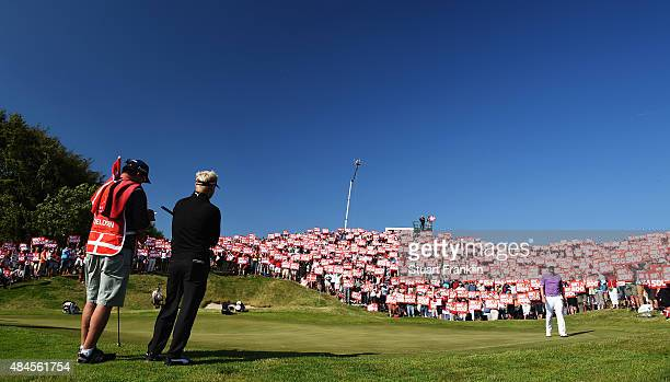 Soren Kjeldsen of Denmark watches on the 16th green as fans hold placards to celebrate the 500th tournement during the first round of the Made in...
