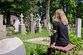 Sorrow woman shrinked near father husband tomb in cemetery.