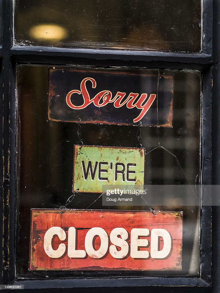 'Sorry we're closed', old signs in a shop window : Stock Photo