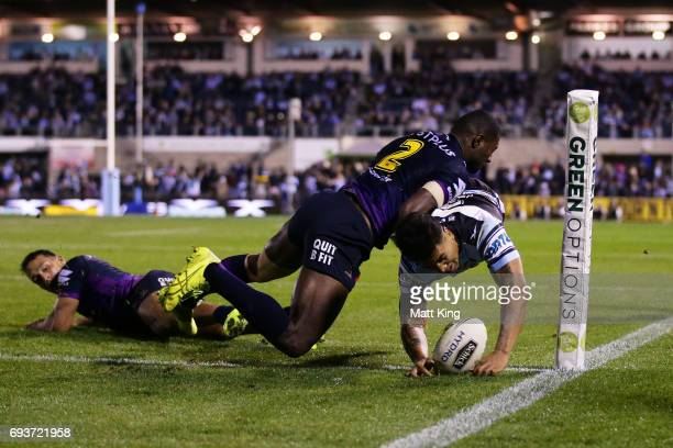 Sosaia Feki of the Sharks beats Suliasi Vunivalu of the Storm to score in the corner during the round 14 NRL match between the Cronulla Sharks and...