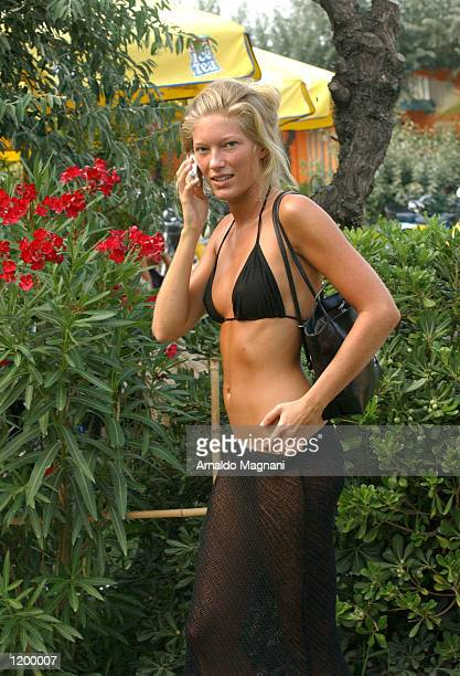 Sosia Della Michelle Hunziker companion to singer Eros Ramazotti uses a cellular telephone July 31 2002 in Milan Italy