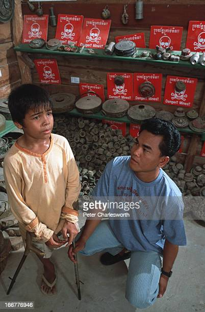 Sot Tol sits with his crutches with his adoptive father Aki Ra in the Landmine Museum that Aki Ra built near Siem Reap Sot Tol lost his leg to a land...