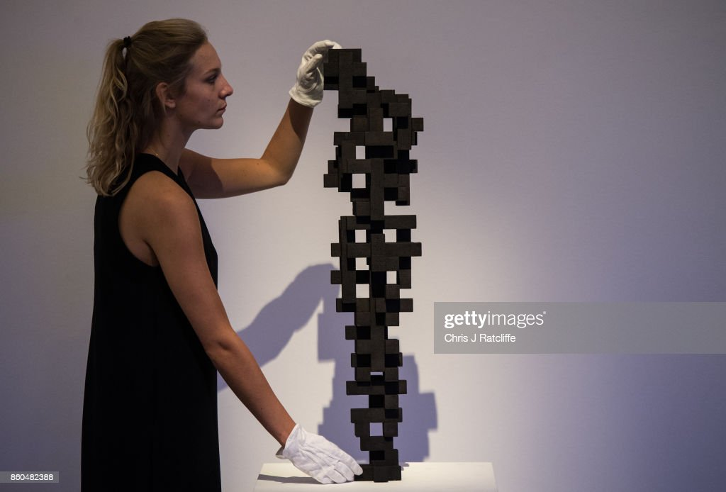 A Sotheby's art handler poses for photographs next to Small Charge by Anthony Gormley, estimated at £120,000-£180,000, during an Art for Grenfell press call at Sotheby's Art for Grenfell preview on October 12, 2017 in London, United Kingdom. The 'Art for Grenfell' auction will take place on October 16 2017 and includes work by contemporary artists.
