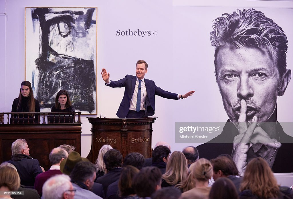 Sotheby's auctioneer Oliver Barker fields bids at the white-glove sale of David Bowie's personal art collection on November 10, 2016 in London, England. He stands in front of Peter Lanyon's 'Witness' which sold for a record £797,000. Tonight's top lot was Jean-Michel Basquiat's Air Power, which more than doubled its estimate to sell for £7,093,000.