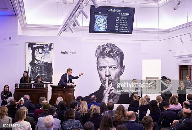 Sotheby's auctioneer Oliver Barker fields bids at the whiteglove sale of David Bowie's personal art collection on November 10 2016 in London England...