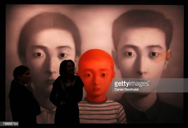 Sotheby's employe stand in fron of a piece by Zhang Xiaogang called big family number 1 during a press preview for Sotheby's Evening Auction of...