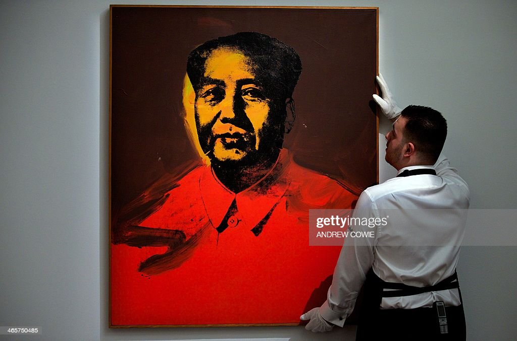 A Sotheby's employee adjusts Andy Warhol's 'Mao' during the Sotheby's Impressionist, Modern & Contemporary Art auctions press preview in London on January 29, 2014. AFP PHOTO/ANDREW COWIE CAPTION