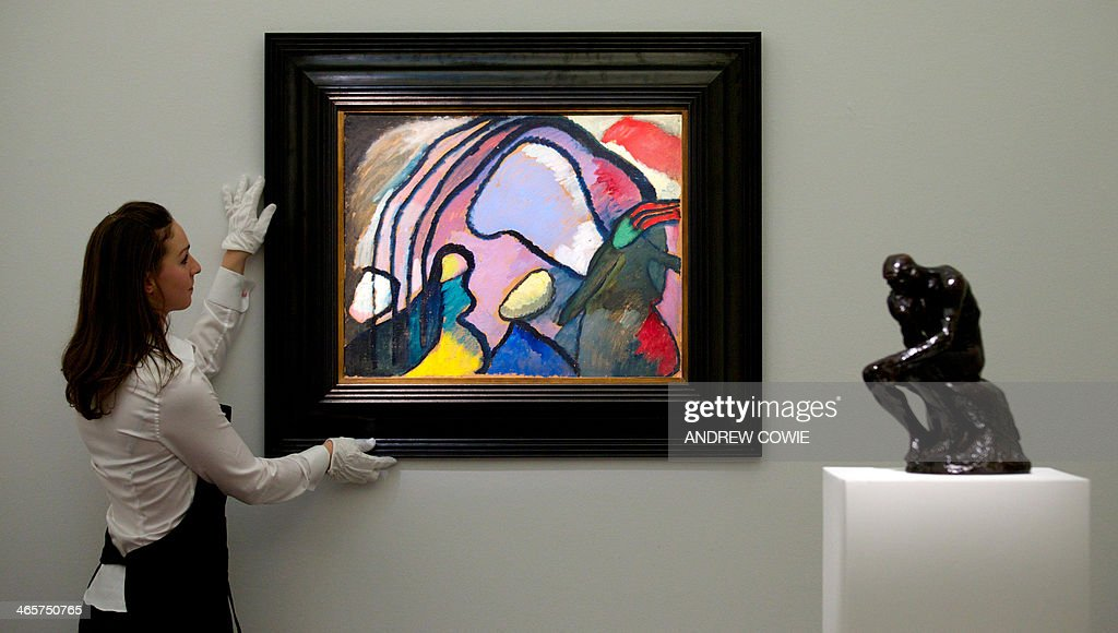 A Sotheby's employee adjusts Wassily Kadinsky's 'Studie fur improvisation 10' (1910) during the Sotheby's Impressionist, Modern & Contemporary Art auctions press preview in London on January 29, 2014.