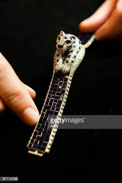 A Sotheby's employee holds a 1984 platinum diamond and sapphire 'Panthere' Cartier wristwatch at Sotheby's auction house in London on March 15 2010...