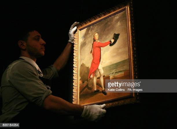 A Sotheby's employee holds a portrait of Major George Maule a painting by Johann Zoffany owned by Gianni Versace and one of the items from his Lake...