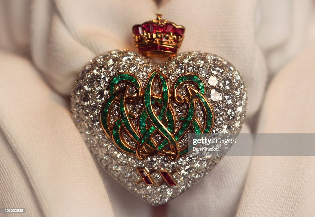 A Sotheby's employee holds an emerald, ruby and diamond broach created by Cartier in 1957, during a preview at Sotheby's Auction House on July 22, 2010 in London, England. This piece of jewellery is one of a collection going on sale including a selection of iconic jewels belonging to the Duchess of Windsor. The pieces are estimated to fetch in the region of £3 million GBP at the sale, which takes place at Sothebys Auction house on November 30, 2010 in London.