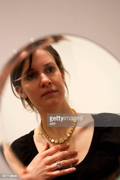 A Sotheby's employee looks at herself in a mirror as she wears a Fancy Intense Pinkish Orange Diamond ring and a Fancy Vivid Yellow Diamond necklace...