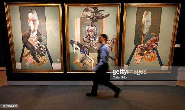 Sotheby's employee passes in front of Francis Bacon's triptych on April 14 2008 in London England The artwork estimated to sell for 70 million GBP is...