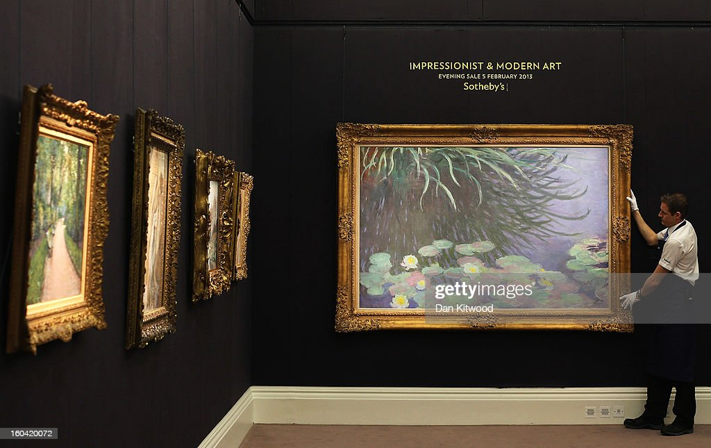 A Sotheby's employee poses in front of a painting by Claude Monet entitled 'Nympheas avec reflects de hautes herbes,' on January 31, 2013 in London, England. The piece makes up a selection of works by artists including Monet, Miro, Picasso and Richter and is estimated to sell for between 12-18 Million GBP at auction in the 'Impressionist and Modern Art' evening sale at Sotheby's auction house on February 5, 2013.