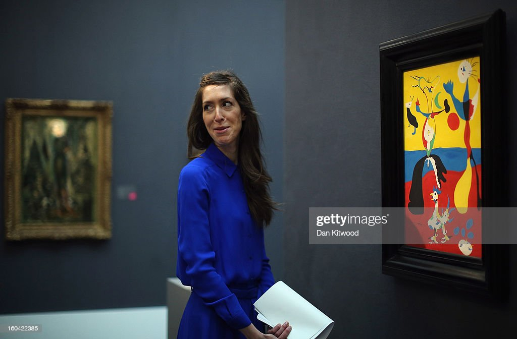 A Sotheby's employee poses in front of a painting by Joan Miro entitled 'Le Fermier Et Son Epouse,' 1932, on January 31, 2013 in London, England. The piece makes up a selection of works by artists including Monet, Miro, Picasso and Richter and is estimated to sell for between 5.5-7.5 Million GBP at auction in the Surrealist Art' evening sale at Sotheby's auction house on February 5, 2013.