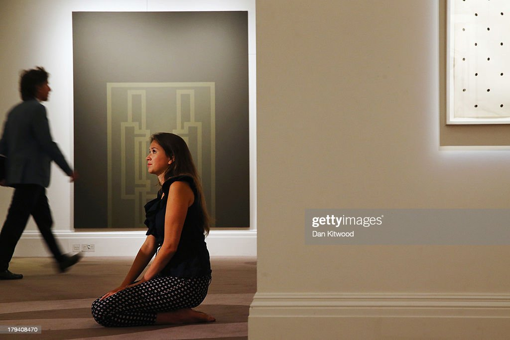 A Sotheby's employee poses in front of a piece of work entitled 'Stand Point' by Robyn Denny at Sotheby's auction house on September 3, 2013 in London, England. The piece makes up part of 'The New Situation' exhibition, comprising of 1960's British Art including paintings by David Hockney and Bridget Riley. The exhibition runs at the auction house until September 11.