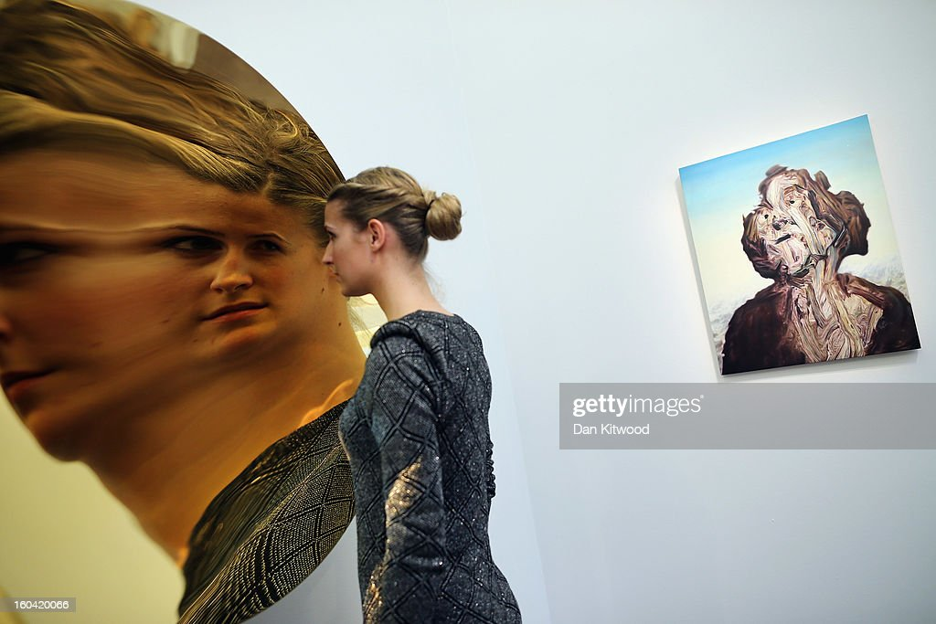 A Sotheby's employee poses in front of an untitled piece by Britsih artist Anish Kapoor on January 31, 2013 in London, England. The piece makes up a selection of works by artists including Monet, Miro, Picasso and Richter and is estimated to sell for between 450,000- 650,000 GBP at auction in the 'Contemporary Art' evening sale at Sotheby's auction house on February 12, 2013.