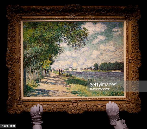 A Sotheby's employee poses with a painting by late French impressionist painter Claude Monet entitled 'La Seine a Argenteuil' during a preview ahead...