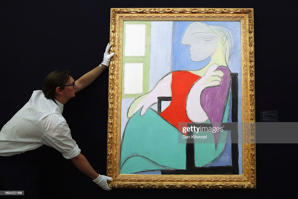 A Sotheby's employee poses with a painting by Pablo Picasso entitled 'Femme assise pres d' une fenetre,' 1932, on January 31, 2013 in London, England. The piece makes up a selection of works by artists including Monet, Miro, Picasso and Richter and is estimated to sell for between 25-35 Million GBP at auction in the 'Impressionist and Modern Art' evening sale at Sotheby's auction house on February 5, 2013.