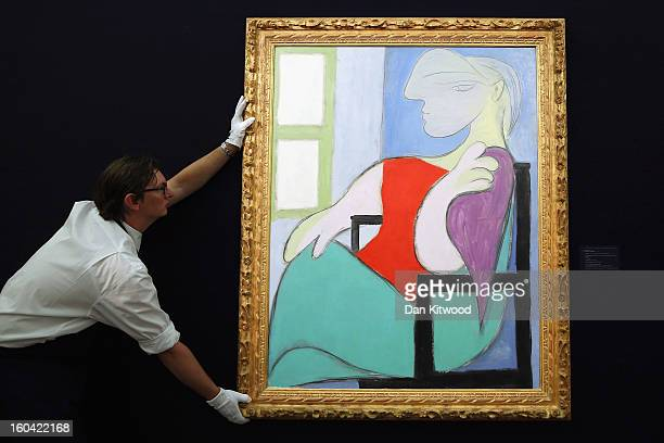 Sotheby's employee poses with a painting by Pablo Picasso entitled 'Femme assise pres d' une fenetre' 1932 on January 31 2013 in London England The...