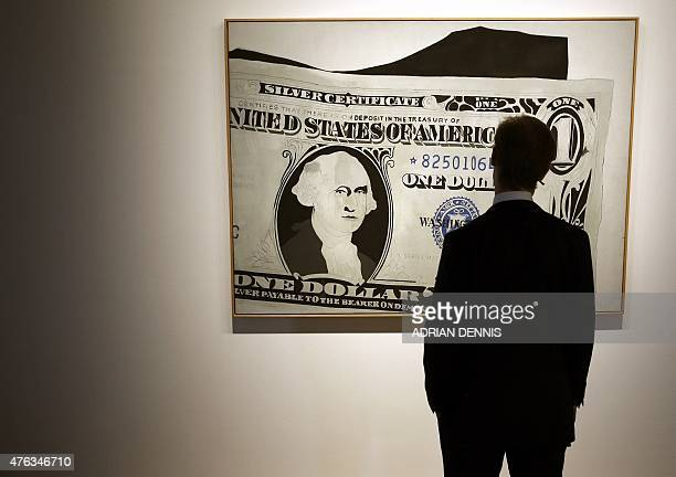 A Sotheby's employee poses with a piece of artwork entitled 'Silver Certificate' an acryllic on canvas by US artist Andy Warhol valued at 1318...
