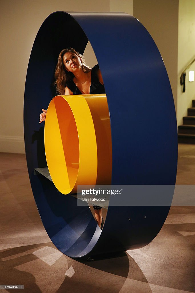A Sotheby's employee poses with an untitled piece of work by David Annesley at Sotheby's auction house on September 3, 2013 in London, England. The piece makes up part of 'The New Situation' exhibition, comprising of 1960's British Art including paintings by David Hockney and Bridget Riley. The exhibition runs at the auction house until September 11.