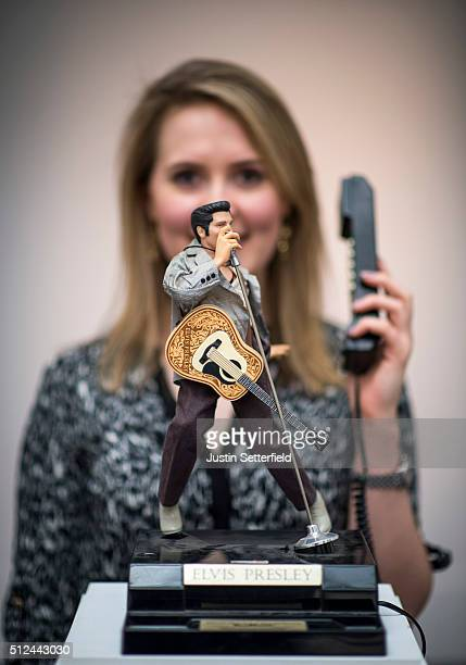 Sotheby's employee stands behind a novelty Elvis telephone during the preauction preview of the personal collection of Deborah Cavendish Duchess of...
