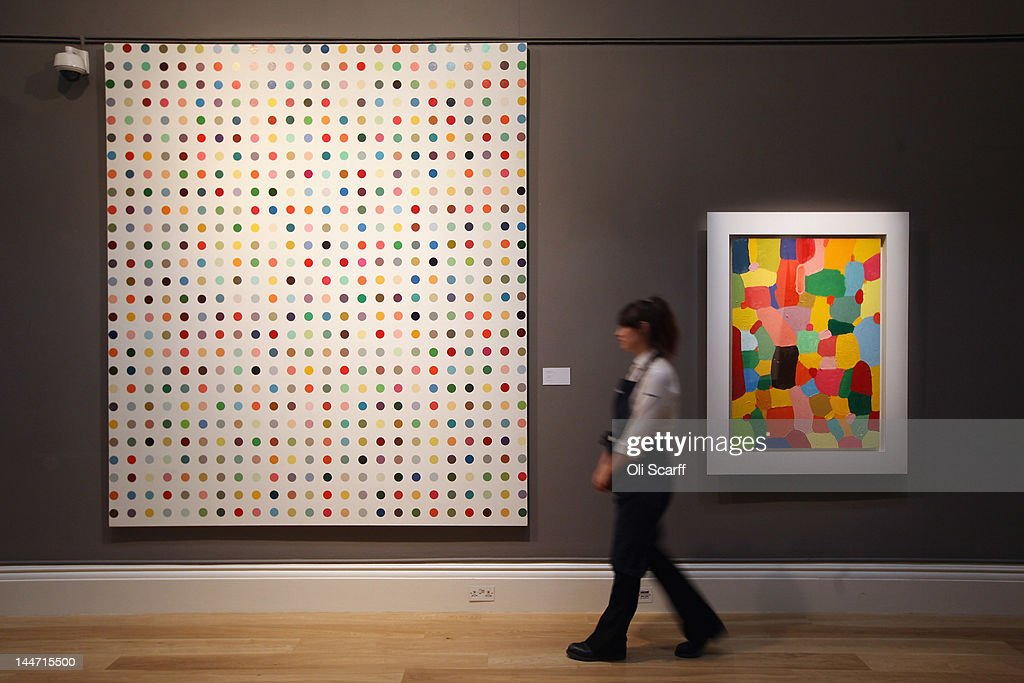 A Sotheby's employee walks past artworks by Damien Hirst entitled 'Chloroacetic Acid' (L) and 'Jolly' on May 18, 2012 in London, England. The artworks feature in Sotheby's forthcoming Contemporary Art sale which is to be held on June 26 and 27, 2012.