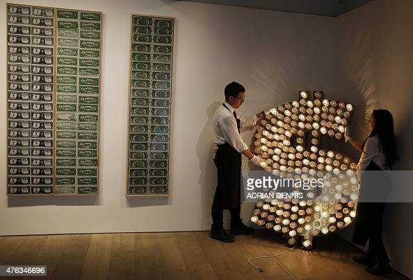 Sotheby's employees pose with a piece of artwork entitled '$' made from reflector caps lamps and an electronic sequencer by artists Tim Noble and Sue...