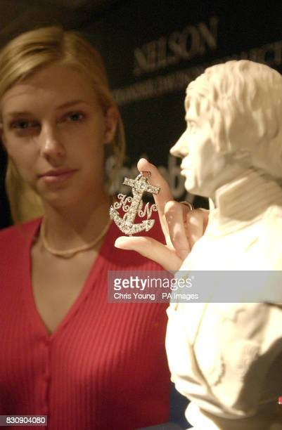 Sotheby's expert Julia Charteris adjusts the brooch with diamond set initials 'HN' believed to have belonged to Lord Nelson that is a part of a...
