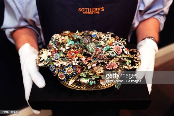A Sotheby's porter holds an exqusite late 17th centuary royal presentation 'basket of flowers' jewel casket a fantasy creation in jewelled and...