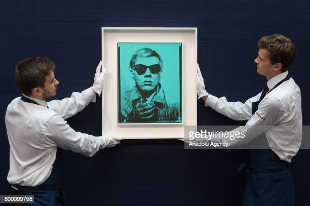 Sotheby's staff hold a self portrait silk screen print of artist Andy Warhol with a sale estimate of £5000£7000 in London United Kingdom on June 23...