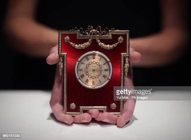 A Sotheby's staff member holding a Faberge gold and enamel timepiece dating from 19081913 and estimated at pound120000180000 during a press preview...