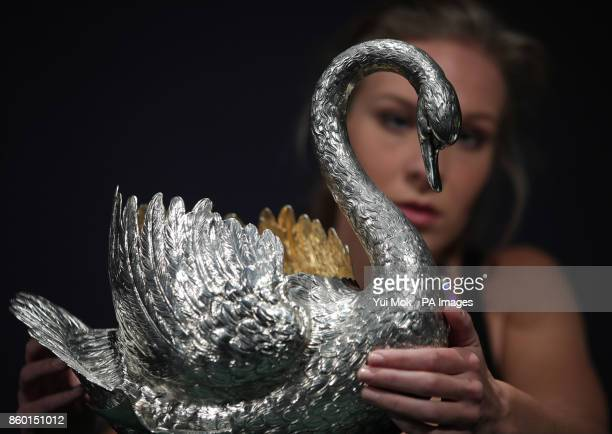 A Sotheby's staff member holding a German table centrepiece in the form of a swan circa 1900 and estimated at pound30005000 during a press preview...