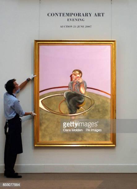 Sothebys staff Wyndham Plumptre adjusts Francis Bacon's 'Self Portrait' at Sothebys auction house in London