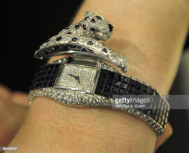 A Sotheby's staffer shows off a saphire and diamond 'Panthere' wristwatch by Cartier circa 1985 April 16 2010 from the collection of Patricia Kluge...