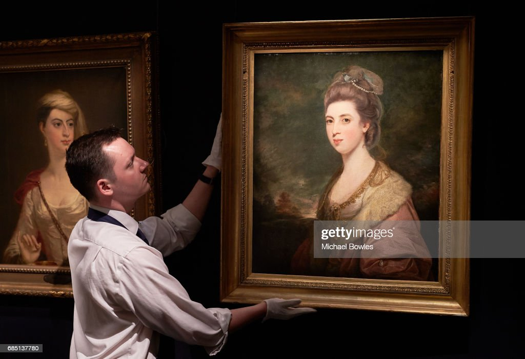A Sotheby's technician adjusts 'Portrait of Mrs Richard Pennant' by Sir Joshua Reynolds, as part of the Ballyedmond Collection at Sotheby's on May 19, 2017 in London, England.