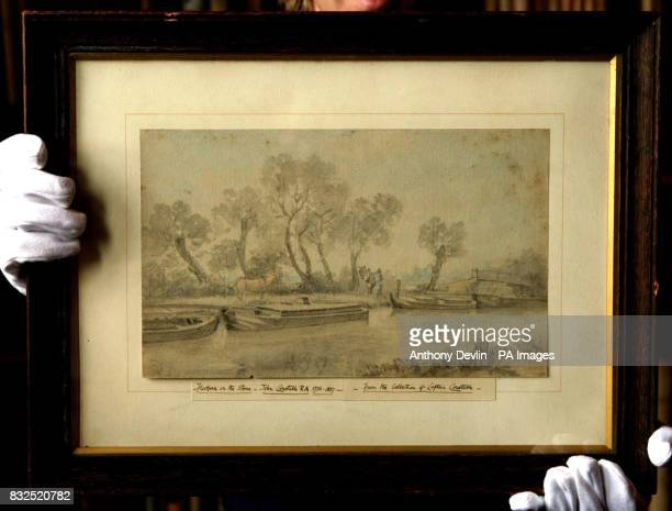 A Sotherby's technician showsoff Lot 75 Barges on the River Stour at Flatford by John Constable which is expected to fetch between 4060 at the...