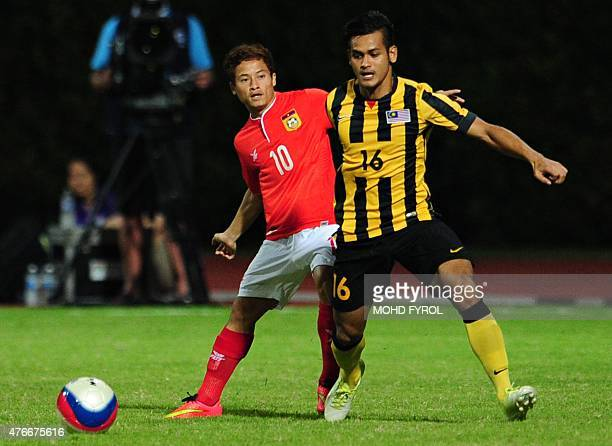 Souk Aphone Vongchiengkham of Laos challenge the ball against Muhammad N Abu Hassan Saari of Malaysia during their first round Group B football match...