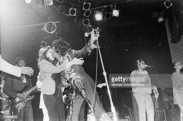Soul singer James Brown gets attacked for a kiss by an amorous fan who jumped on stage from the audience in circa 1980