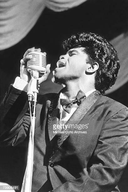Soul singer James Brown sings in to a vintage microphone as he performs onstage in 1964 in New York New York