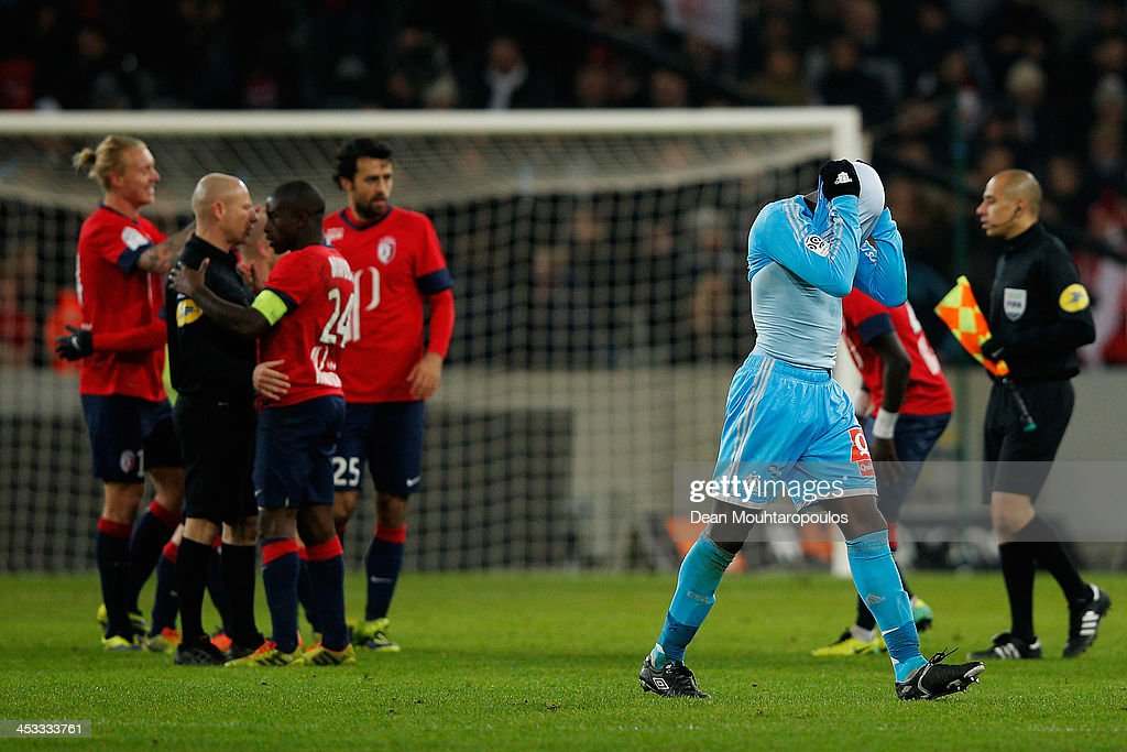 <a gi-track='captionPersonalityLinkClicked' href=/galleries/search?phrase=Souleymane+Diawara&family=editorial&specificpeople=695613 ng-click='$event.stopPropagation()'>Souleymane Diawara</a> of Marseille looks dejected as he reacts to defeat by pulling his shirt over his head after the final whistle as Lille players celebrate during the Ligue 1 match between LOSC Lille and Olympique de Marseille held at Stade Pierre-Mauroy on December 3, 2013 in Lille, France.