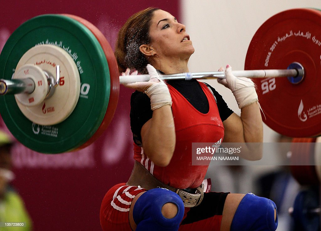 Soumaya Fatnassi attempts to lift 101kgs in the Clean and Jerk weightlifting for the women's 53kg category at the Arab Games in Doha on December 13...