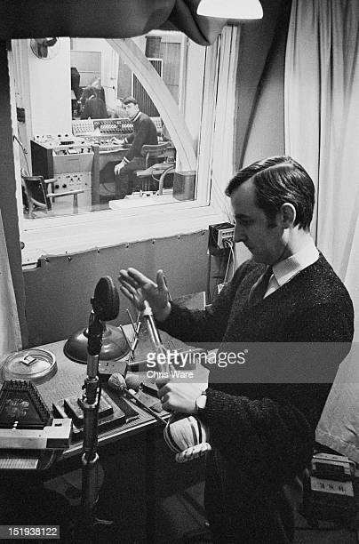 Sound engineer Dick Mills creates a sound effect by hitting the neck of an open bottle in a sound booth in the BBC Radiophonic Workshop at the BBC's...