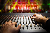 sound engineer hands working on sound mixer, background of concert stage