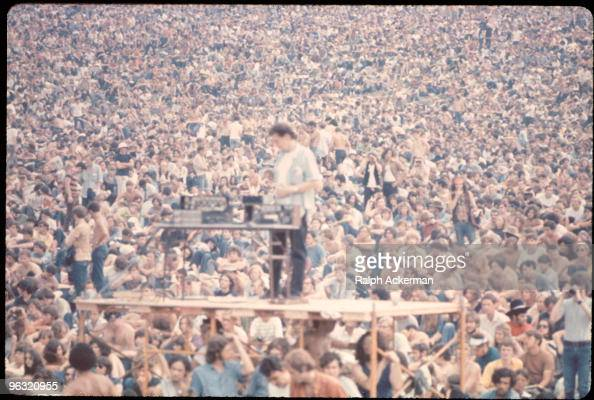 A sound guy stands on scaffolding with his equipment in front of the crowd at the Woodstock music festival August 1969