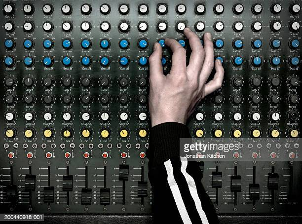 Sound technician adjusting dial on mixing desk, close-up