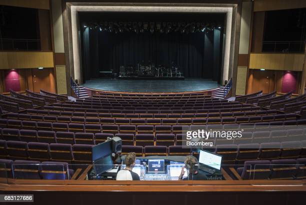 Sound technicians sit behind an audio console in the Royal Theater on board the Ovation of the Seas Quantumclass cruise ship operated by Royal...
