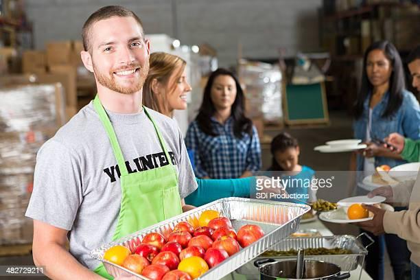 Cocina libre en voluntarios hombres sosteniendo una bandeja de frutas